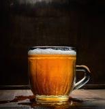 Verre de vintage de bière avec la mousse sur un conseil en bois sur un fond foncé photo libre de droits