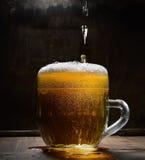 Verre de vintage de bière avec la mousse sur un conseil en bois sur un fond foncé image libre de droits