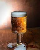 Verre de vintage de bière avec la mousse sur un conseil en bois sur un fond foncé photographie stock