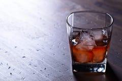Verre de whiskey avec de la glace naturelle sur une table en bois Images libres de droits
