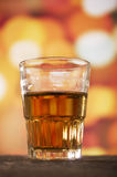 Verre de whiskey de rhum au-dessus des lumières defocused Images stock