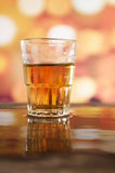 Verre de whiskey de rhum au-dessus des lumières defocused Photo libre de droits