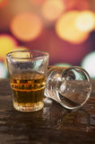 Verre de whiskey de rhum au-dessus des lumières defocused Photo stock