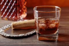 Verre de whiskey et de cigare sur la vieille table en bois photo stock