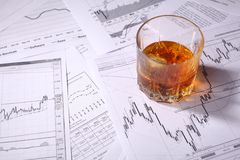 Verre de whiskey sur des diagrammes Photos stock