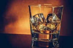 Verre de whiskey sur la table noire avec la réflexion et le fond d'or, l'atmosphère chaude photos stock