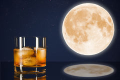 Verre de whiskey sur le ciel de minuit avec le fond de pleine lune Photo stock