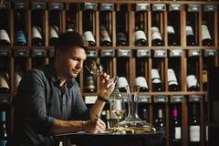 Verre degustating de vin blanc de Sommelier dedans vers? images stock
