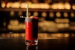 Verre du cocktail rouge salé de bloody mary de tomate décoré du sel et des olives avec le staw photographie stock libre de droits