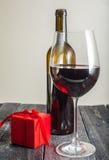 Verre du vin rouge et d'un cadeau sur un fond en bois Images libres de droits