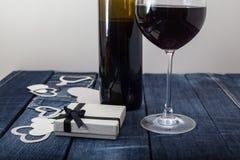 Verre du vin rouge et du cadeau sur le fond de denim Photographie stock libre de droits