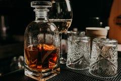 Verre du whiskey avec de la glace et un décanteur carré sur un fond noir Photo libre de droits