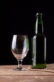 Verre et bouteille avec de la bière sur la table en bois Images libres de droits