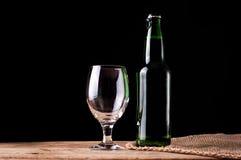 Verre et bouteille avec de la bière sur la table en bois Image libre de droits