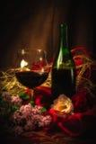 Verre et bouteille de vin rouge dans l'arrangement élégant sous la lumière molle Photographie stock