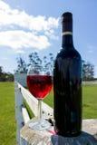 Verre et bouteille de vin rouge sur un poteau et une barrière de rail en bois blancs Images libres de droits
