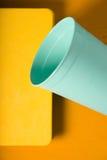 Verre et carnet en plastique de turquoise sur un fond jaune photographie stock