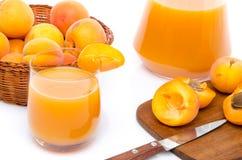 Verre et cruche de jus d'abricot avec un panier des abricots et du sli Photo stock
