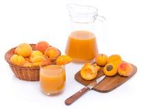 Verre et cruche de jus d'abricot avec un panier des abricots et du sli Image stock