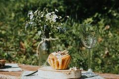 Verre et gâteau sur une table ensoleillée, un bouquet des fleurs de ressort pour l'humeur photos libres de droits
