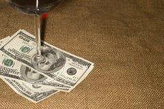 Verre et quelques billets de banque des USA $100 sur le vieux tissu Images libres de droits