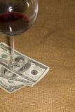 Verre et quelques billets de banque des USA $100 sur le vieux tissu Photo stock