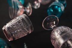 Verre et tasses colorés sur un fond noir photographie stock