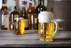 Verre facetté de bière blonde avec la mousse photographie stock libre de droits