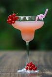 Verre formé avec le cocktail de pamplemousse rose sur le bokeh vert de fond Images stock