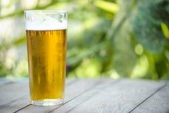 Verre froid de bière dessus sur une table en bois Photographie stock