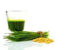 Verre à liqueur d'herbe de blé avec l'herbe de blé de coupe et le blé frais Images stock