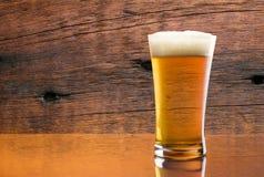 Verre magnifique de bière délicieuse avec le fond en bois de grange Photos stock