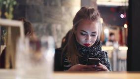 Verre mening van een mooi blondemeisje die met heldere rode lippenstiften Internet surfen Modieus kijk Café stock videobeelden
