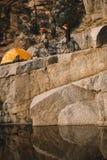 verre mening van twee mannelijke reizigers die zich met bergfietsen dichtbij tent op rotsachtige klip bevinden royalty-vrije stock foto's
