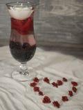 Verre rempli dans le sable avec un coeur des roses images stock