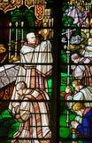 Verre souillé - un évêque tenant un ostensoir images stock