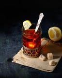 Verre-support de vintage sur la serviette tricotée avec la tasse de thé avec les cubes découpés en tranches en citron et en sucre images stock