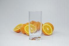 Verre vide et moitiés des oranges Photographie stock