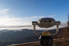Verrekijkers die uit de winterberg kijken Stock Foto