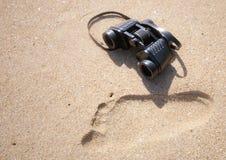 Verrekijkers naast een menselijke voetafdruk het zand Royalty-vrije Stock Afbeeldingen
