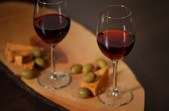 Verres à vin avec le vin rouge sur le bois avec du fromage et les olives vertes - pour la soirée à la maison confortable Photo stock