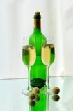 Verres à vin, une bouteille et sucreries sur le miroir Photo libre de droits