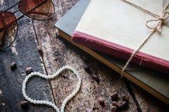 Verres attachés avec une corde dans un livre avec les andnuts en forme de coeur de perles Image stock