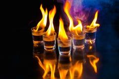 Verres avec de l'alcool brûlant sur le fond noir Photographie stock