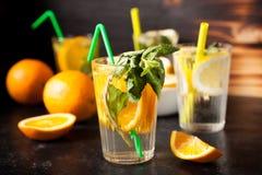 Verres avec de l'eau naturel avec des tranches d'oranges et de citrons dans lui photos stock