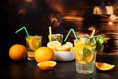 Verres avec de l'eau naturel avec des tranches d'oranges et de citrons dans lui image stock