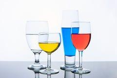 Verres avec de l'eau rouge, jaune, et bleu photos libres de droits