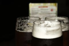 Verres avec de la bière foncée sur la barre photos stock