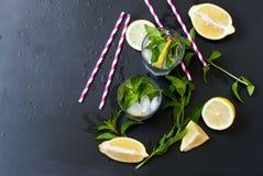 Verres avec de la glace et citron, menthe et glace sur un fond noir Photo libre de droits