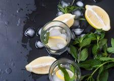 Verres avec de la glace et citron, menthe et glace sur un fond noir Photos stock